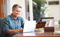 smiling gray haired man in home office looking at laptop